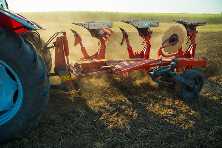 stubble: Farmer plowing stubble field with red tractor