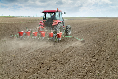 seeding: Farmer sowing crops with pneumatic seeding machine Stock Photo