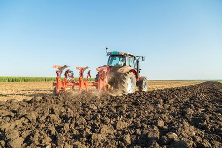 arando: Agricultor arando campo de rastrojos con el tractor rojo Foto de archivo
