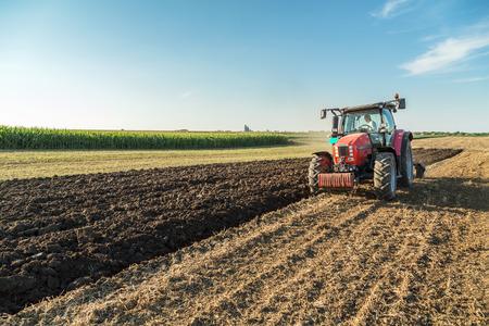 Agricultor arando campo de rastrojos con el tractor rojo