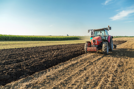 agriculture machinery: Farmer plowing stubble field with red tractor