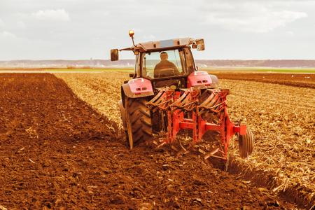 stubble field: Farmer plowing stubble field with red tractor