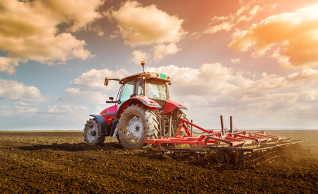 Farmer in tractor preparing land with seedbed cultivator Stok Fotoğraf - 52263609