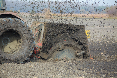 trencher: Tractor with double wheeled ditcher digging drainage canal
