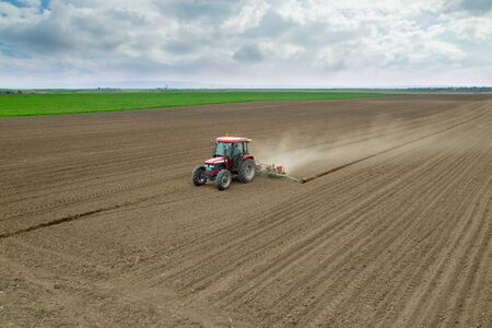 seed drill: Farmer sowing crops at field with tractor