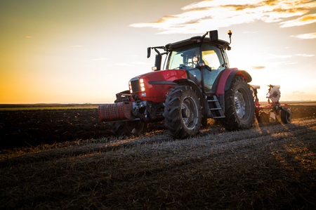 Farmer plowing stubble field with red tractor at sunset Stock Photo