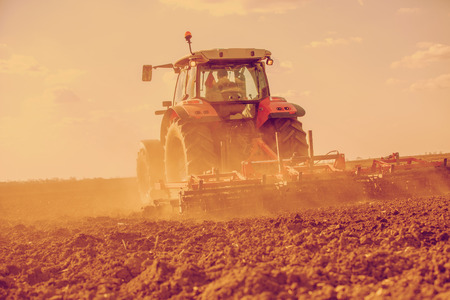 seed bed: Farmer in tractor preparing land with seedbed cultivator. Filtered image. Stock Photo