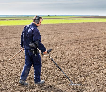 detecting: Man searching for treasure with metal detector