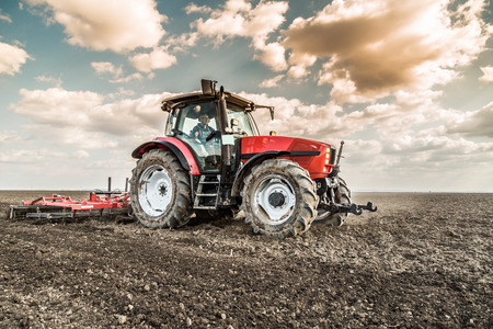 Rolnik z ciągnika przygotowuje grunt rozsadnik