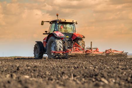 Landbouwer in tractor voorbereiding van grond met zaaibed cultivator