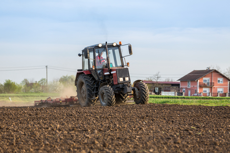 Farmer cultivating arable land before seeding
