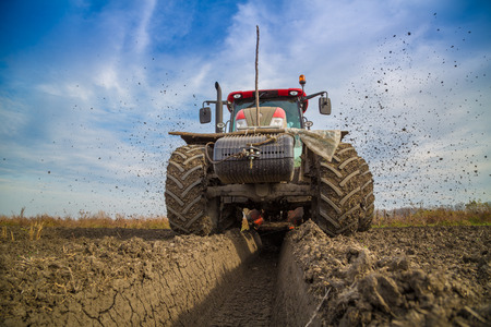 Tractor with double wheeled ditcher digging drainage canal