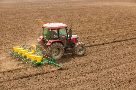 seeding: Farmer seeding, sowing crops at field Stock Photo