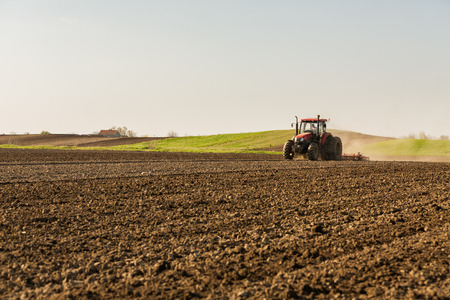 the arable land: Farmer in tractor preparing land with seedbed cultivator