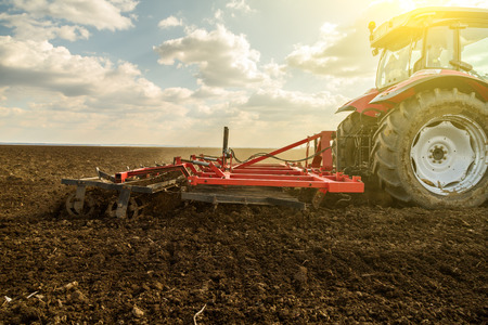 the arable land: Farmer in tractor preparing land with seedbed cultivator as part of pre seeding activities in early spring season of agricultural works at farmlands.