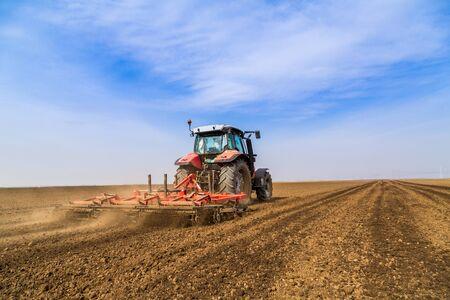 arando: Farmer in tractor preparing land with seedbed cultivator