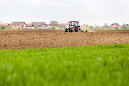 Farmer seeding, sowing crops at field. Sowing is the process of planting seeds in the ground as part of the early spring time agricultural activities.