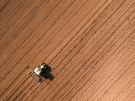 Aerial shot of a farmer seeding, sowing crops at field. Sowing is the process of planting seeds in the ground as part of the early spring time agricultural activities. Imagens