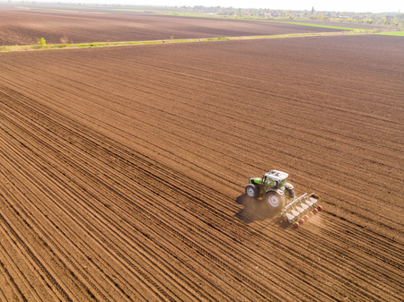 Aerial shot of a farmer seeding, sowing crops at field. Sowing is the process of planting seeds in the ground as part of the early spring time agricultural activities. Stock Photo