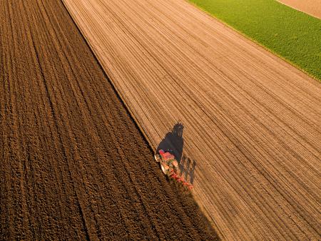 Aerial shot of a farmer plowing stubble field