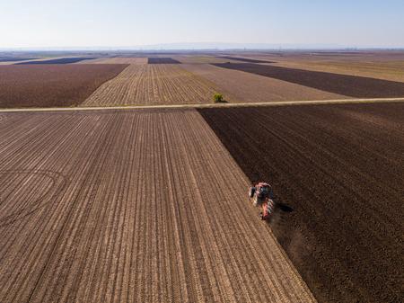 Aerial shot of a farmer plowing stubble field Reklamní fotografie - 104125678