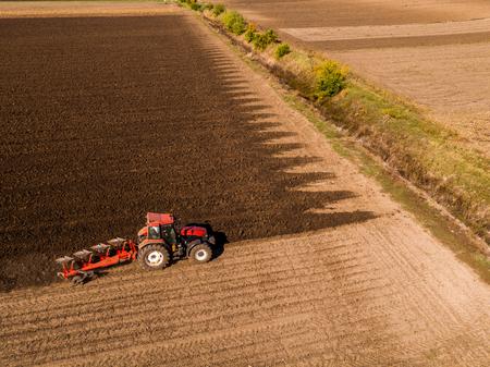 Aerial shot of a farmer plowing stubble field