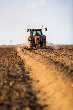 Farmer in tractor preparing land with seedbed cultivator as part of pre seeding activities in early spring season of agricultural works at farmlands.