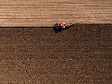 Aerial shot of a farmer plowing stubble field Reklamní fotografie - 104125264