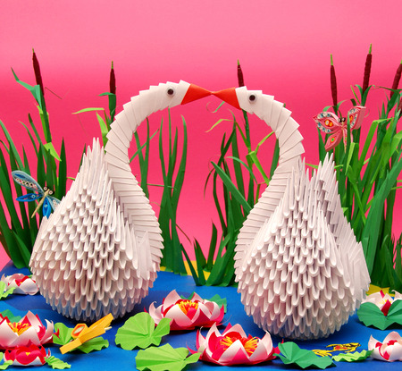 Origami work swans and beautiful background with ponds and grass photo