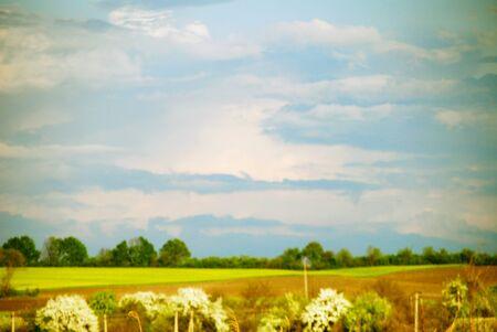 sfondo nuvole: Offuscata paesaggio rurale, un villaggio in background, nuvole e campi