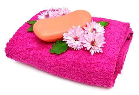 Towels, soap and flowers isolated on white background