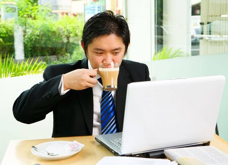 Situated inside the café that surrounded by glass wall, he is working with his laptop while drinking the coffee. Clean green environment in suburb area of the city as the background photo