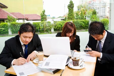 Situated in a café, a group of business people seriously signing the agreement, with clean green environment of suburb area in the city as background. Stock Photo - 3658902