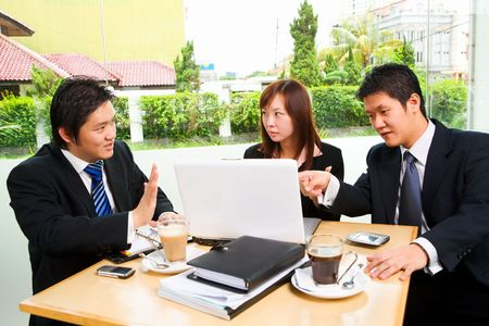 reject: Situated in a café, a group of business people seriously discuss about something, with clean green environment of suburb area in the city as background.
