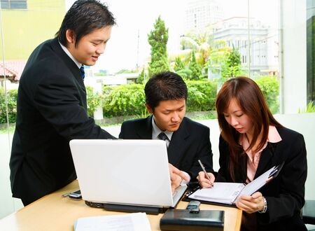 writing activity: The people discuss about rescheduling the job in caf� at lunch break. Clean green environment in suburb area of the city as the background. Stock Photo