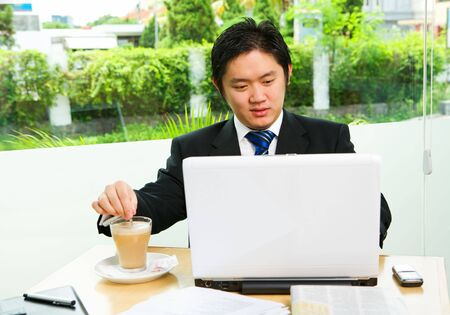 Inside the caf� that surrounded by glass wall; he is working with his laptop while stirring the coffee. Clean green environment in suburb area of the city as the background. photo