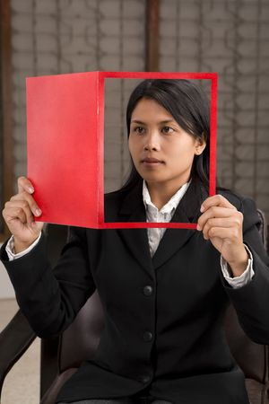 A young businesswoman holding a magazine (look like she reads it) where her face is on cover page. photo
