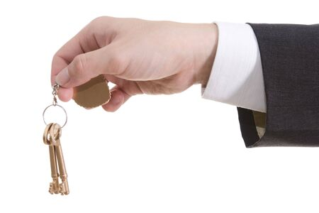 A hand is handing over a pair of keys, against white background photo