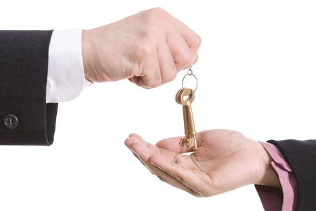 One hand is handing over the keys while the other receives them. Shot against white background. photo