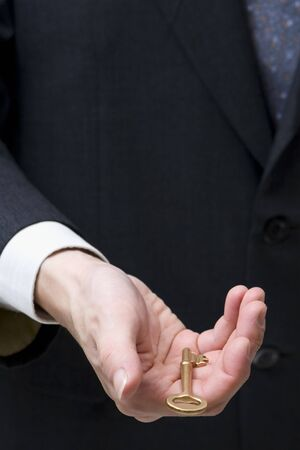 loosely: A hand holding the golden keys in loosely.