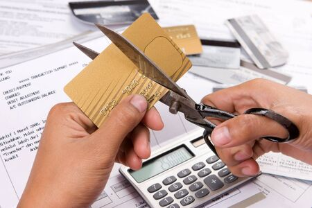 spendthrift: An action of cutting a credit card using a scissors.The number and personal ID of the credit card has been removed or replaced from the original one to prevent unnecessary things. Stock Photo