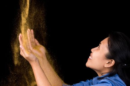 A young woman happily receiving gold dust from above