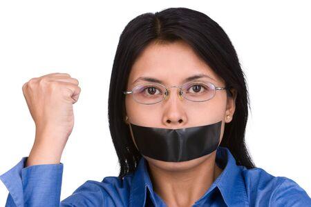 feministische: Een jonge vrouw met haar mond bepleisterd en haar vuist verhoogd. Schiet tegen zeer helder witte achtergrond te scheiden het met het model natuurlijk. Stockfoto