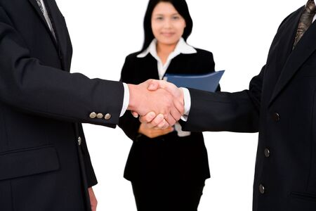 dealt: Two business leader shake hand while a businesswoman witnessing it. Stock Photo