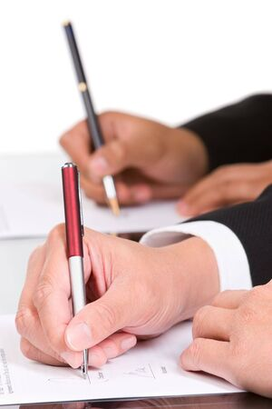 autograph: Two hand is signing the document, focused mainly on the front hand.