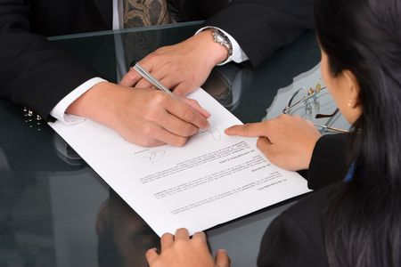 A business woman show the place on the document where the director should sign. photo