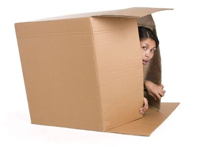 A young woman is hiding inside a box and suspiciously observing around Stock Photo - 3802614