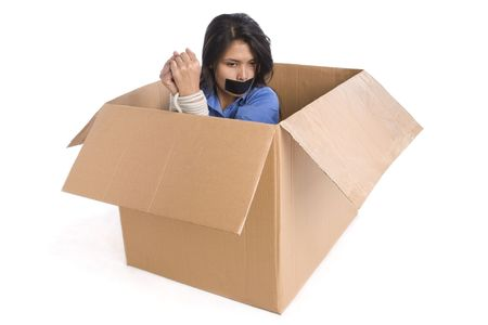 A young woman tied up inside the box is thinking how to escape. Stock Photo