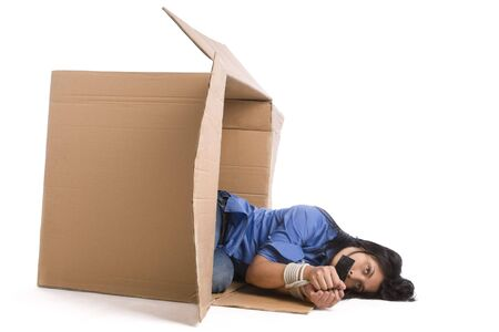 A young woman tied up and plastered on her mouth, falling from the cardboard. Stock Photo