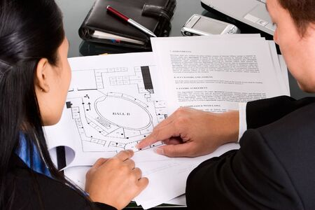discuss: Two business people, man and woman discuss about their property planning.